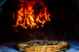 La magie d'un four à pain en argile et une chaleur intense: le secret d'une pizza bien réussie. Fête pizza à la ferme Au Petit boisé, Dunham.